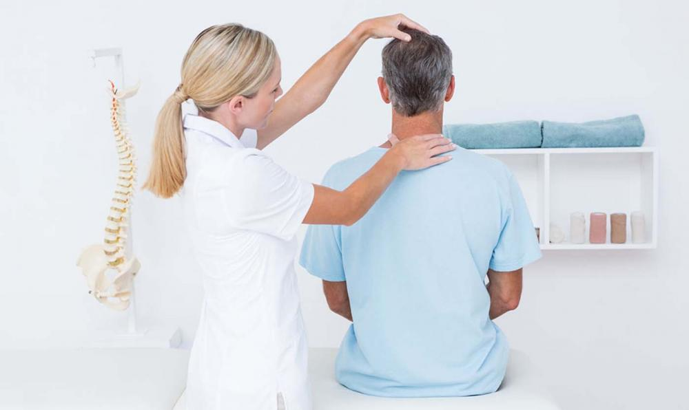 Chiropractor treating a mans whiplash after his car accident